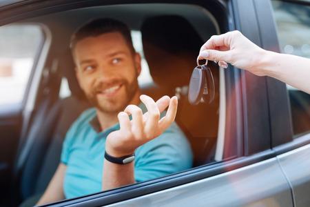 crossover: Beautiful bearded man receiving car keys
