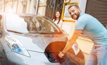 unplugging: Smiling man unplugging the charger from the car