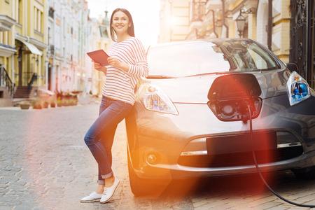 Jeune femme à l'aide de tablette en chargeant la voiture