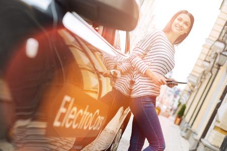 魅力的な女性が彼女の車にタブレットを保持しながら傾いた