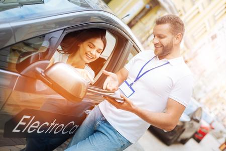 Smiling woman listening to car rental agency employee