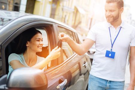 Autoverhuurbedrijf medewerker die auto sleutels geeft aan vrouw