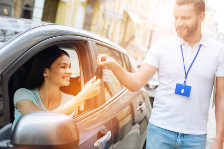 Employé de l'agence de location de voiture donnant des clés de voiture à la femme Banque d'images