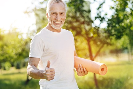 Positive aged smiling getting ready for sport exercises Фото со стока