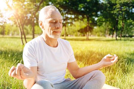 Delighted senior man enjoying yoga in the park