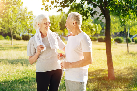 Cheerful senior couple resting together after jogging in the park