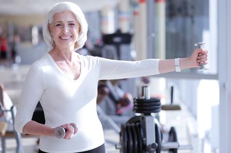 Sonriendo anciana haciendo ejercicio con pesas