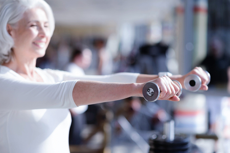 Side view of old lady exercising with dumbbells