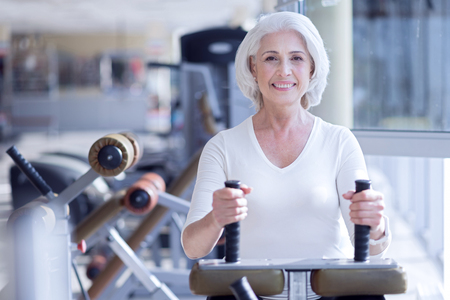 Happy old lady working on fitness machine