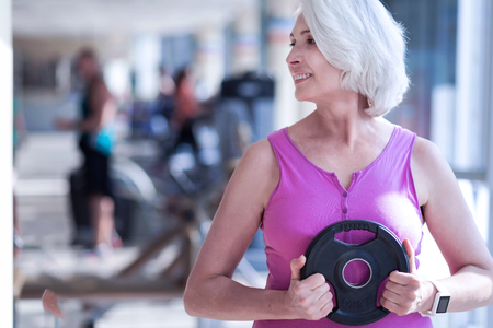 Aged woman holding barbell at gym Stockfoto