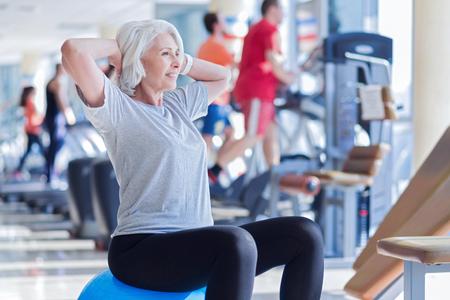 Alte Dame macht Übungen auf Fitness Ball Standard-Bild