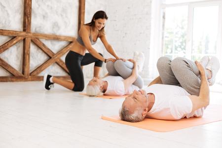 Concentrated elderly man embracing his knees Reklamní fotografie