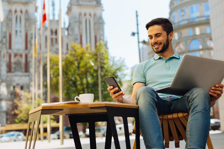 Positive confident guy smiling while reading the message