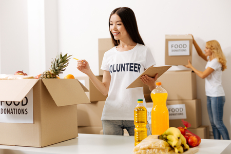 Capable intelligent woman examining the contents of the box Stock Photo
