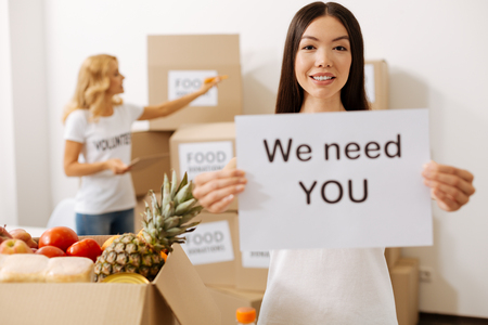 Open minded cheerful woman holding a poster promoting charity
