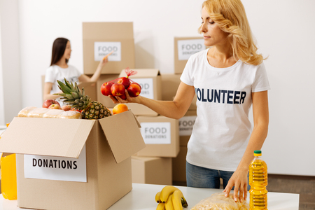 Energetic attentive woman packing fruits