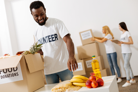 Handsome enthusiastic man helping as a volunteer