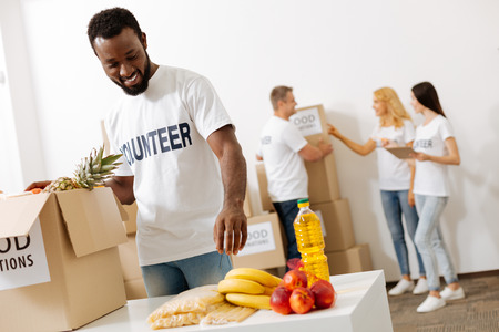 Energetic altruistic man helping packing supplies