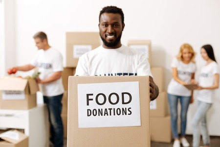 Energetic strong guy carrying a box with donations