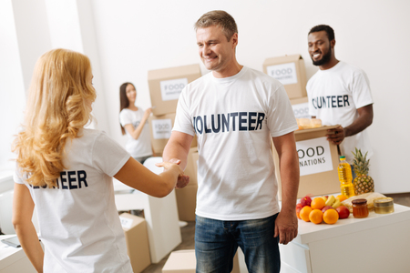 Friendly nice man shaking hands with new volunteer Stock Photo