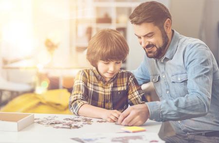 Netter intelligenter Junge , der ein Puzzlespiel mit seinem Vater tut Standard-Bild - 82278479