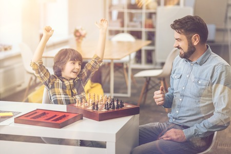 Cheerful delighted boy winning the chess game