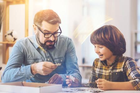 Fröhlicher positiver Vater und Sohn, der ein Puzzle macht