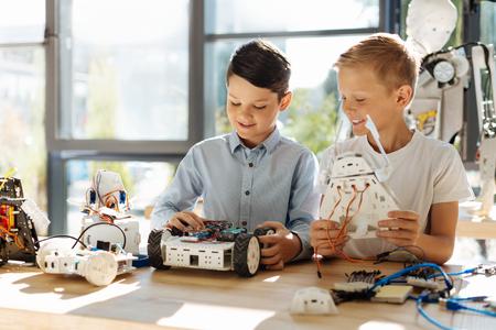 Adorable little boys examining new robots Standard-Bild