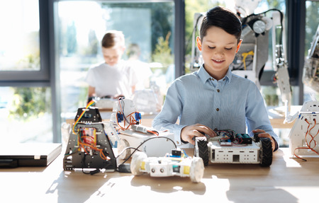 Sweet little boy examining front part of robotic vehicle