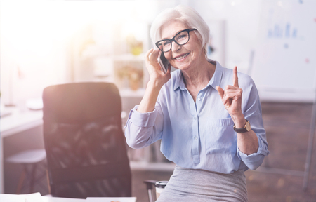 gerontology: Busy ambitious businesswoman asking to hold on