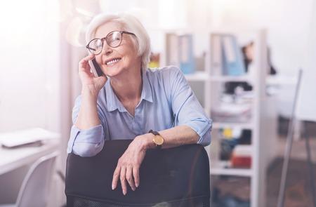 Brilliant positive lady enjoying a conversation Stock Photo