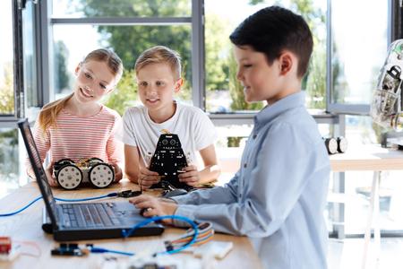 Junge und Mädchen, die ihre Freundarbeit am Laptop aufpassen Standard-Bild - 82793532