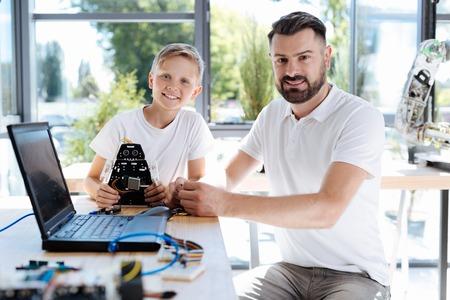 Happy student sitting near his robotics teacher