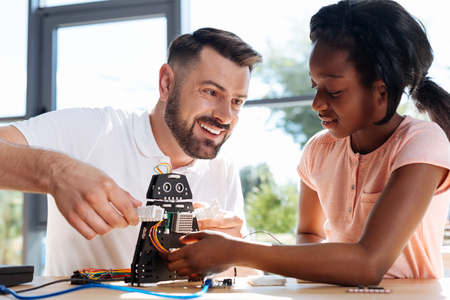 Cheerful teacher and student playing with a robot