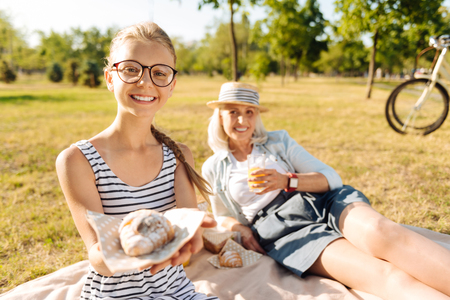 Cute teener girl holding croissant outdoors