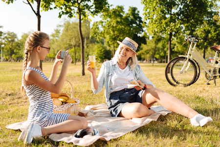 Positive teener girl taking photos of her granny on a picnic Stockfoto