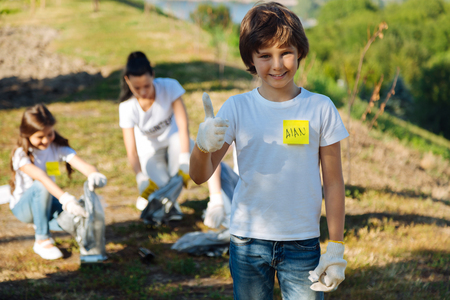 Delighted boy working in volunteer group Stock Photo