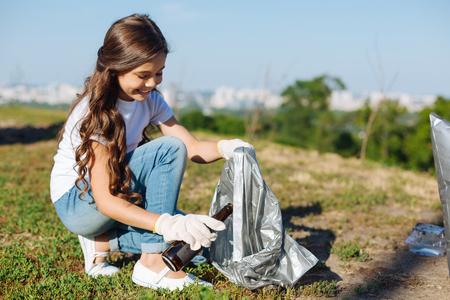 Menina encantadora, segurando um pacote para lixo
