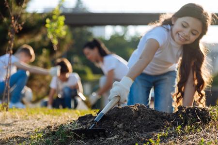 Zorgvuldige langharige brunette staande op de knieën tijdens het tuinieren Stockfoto