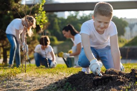 Positiver begeisterter blonder Junge, der Boden harkt Standard-Bild - 82798914