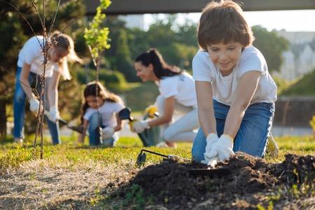 Delighted brunette kid preparing soil for usage