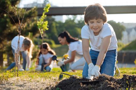 Kind man-child raking ground with pleasure