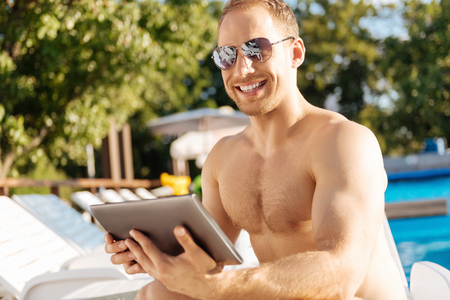 Happy man smiling at the camera while holding tablet