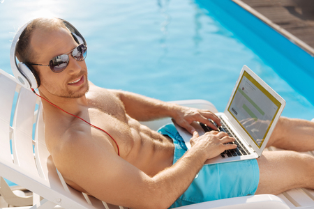 Young man developing an application while sunbathing