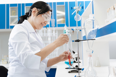 Cheerful female chemist doing an experiment