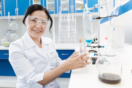 Positive female chemist enjoying her job Stock Photo