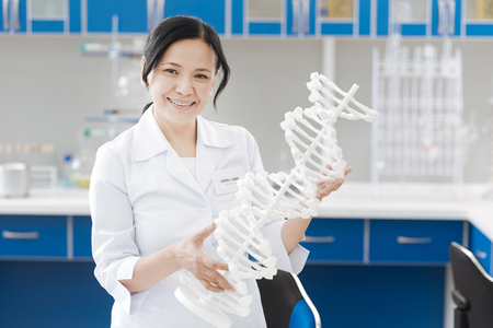 Happy positive woman holding a DNA model