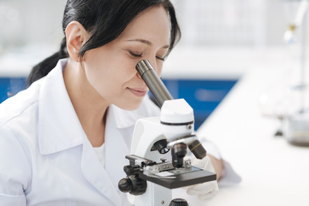 Serious pleasant woman studying microorganisms