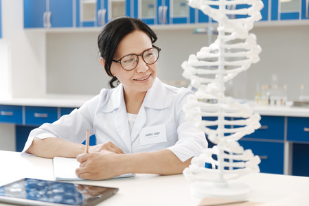 up code: Delighted genetic researcher studying genome Stock Photo