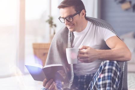 Happy male reading interesting book